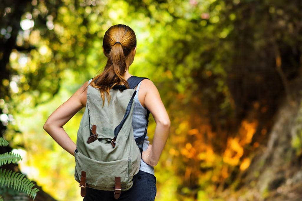 Young woman with the backpack hiking in the forest shot with Nikon portrait lens